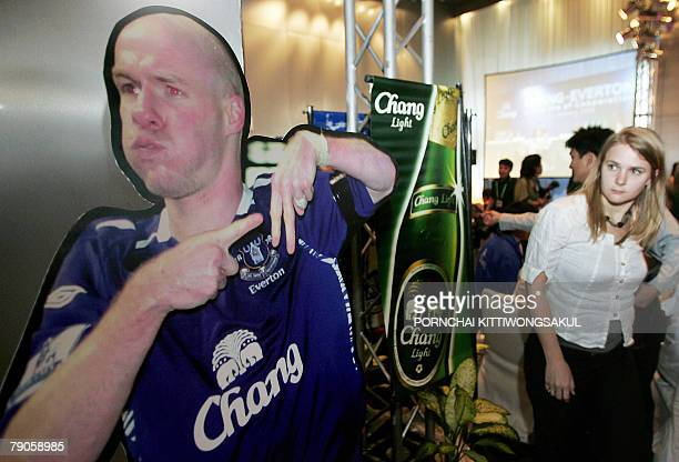 A woman looks at portrait of an Everton football player next to a poster of a Chang bottle beer during a press conference on a sponsorship deal in...