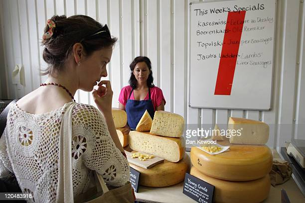 A woman looks at produce on a stall selling cheeses in a railway arch near Maltby Street Market on August 6 2011 in London England The arches on...