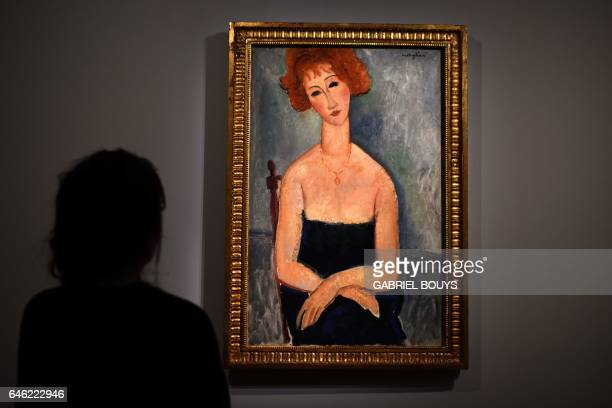A woman looks at 'Redheaded Woman wearing a Pendant' by Amedeo Modigliani during a media preview of the exhibition 'From Zurbaran to Rothko...