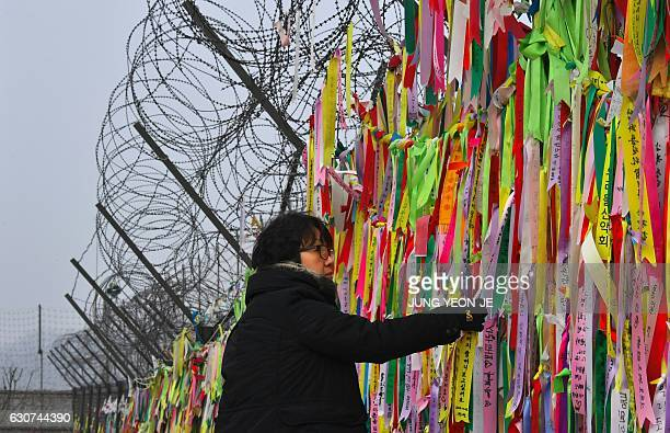 A woman looks at ribbons hanging from a military barbed wire fence calling for peace and reunification at the Imjingak peace park in the border city...