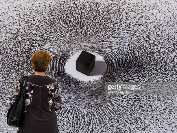 A woman looks at Saudi artist Ahmed Mater's 'Magnetism IV' during an exhibition dedicated to Saudi Arabia's King Salman's first official trip to...
