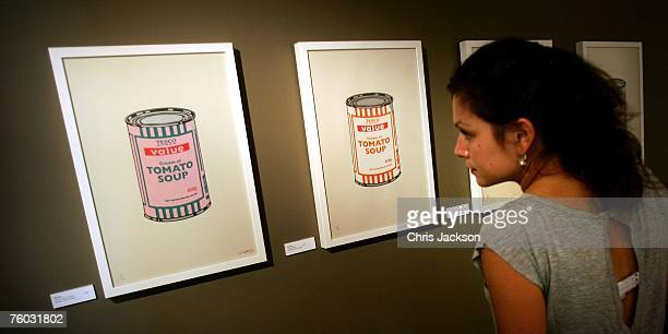 A woman looks at screen prints of Tesco Value Baked Bean cans by Banksy similar to Warhol's iconic Campbell's Tomato Soup prints at the Warhol vs...