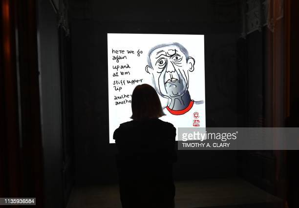 A woman looks at SelfPortraits 20032016 2017 a projection part of two hundred and twenty drawings documenting Leonard Cohens selfportraits during a...