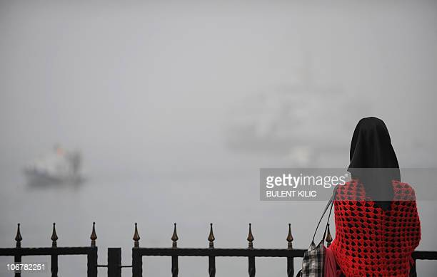 A woman looks at ships in the district of Kadikoy in Istanbul as heavy fog has restricted boat traffic on the Bosphorus river on November 6 2010 AFP...