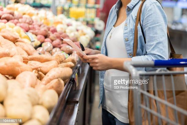 Woman looks at shopping list