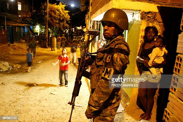 A woman looks at soldiers patroling in the Commune 1 a shantytown with the highest rates of urban violence and displacement due to disputes between...
