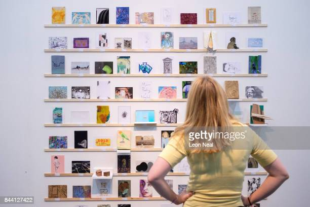 Woman looks at some of the postcards displayed in the RCA Secret Postcard fundraising exhibition at the Royal College of Art on September 8, 2017 in...