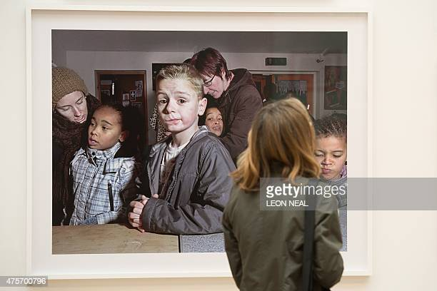 A woman looks at 'Somerford Grove Adventure Playground in Tottenham' by British artist Mark Neville during the press preview of the Royal Academy...