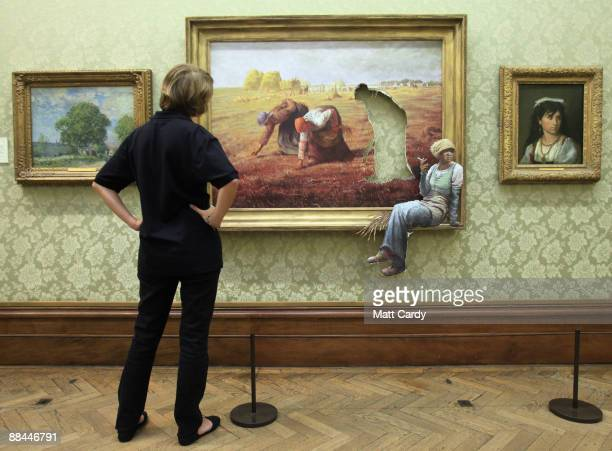 """Woman looks at surprise exhibits by the underground guerrilla artist, Banksy on June 12 2009 in Bristol, England. The exhibition called """"Banksy..."""