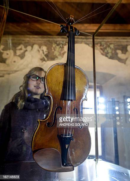 A woman looks at the 1727 violin made by Italian Antonio Stradivari known as the 'Vesuvius' at the museum of the 'Magnifica Comunità di Fiemme'...