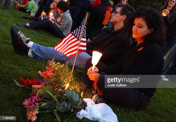 A woman looks at the American flag as she sits in Dolores Park September 14 2001 in San Francisco during a nation wide candlelight vigil held for...