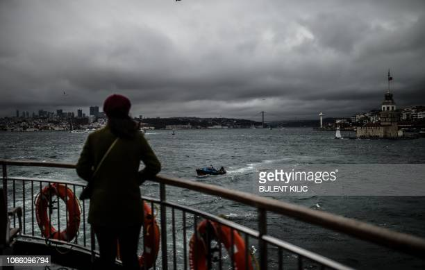 A woman looks at the Bosphorus with the Maidan tower in background from the terrace of a ferry as she travels from Europe to Asia during a storm in...