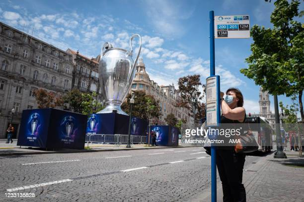 Woman looks at the bus timetable as a giant inflatable UEFA Champions League trophy is displayed in the host city venue of Porto ahead of the UEFA...