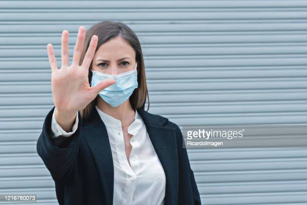 woman looks at the camera and with her hand makes a stop sign while wearing her mask against germs and covid 19 - uncertainty stock pictures, royalty-free photos & images