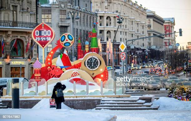 A woman looks at the digital FIFA World Cup 2018 countdown clock placed in front of the Red Square and the Kremlin in Moscow marking 100 days to the...
