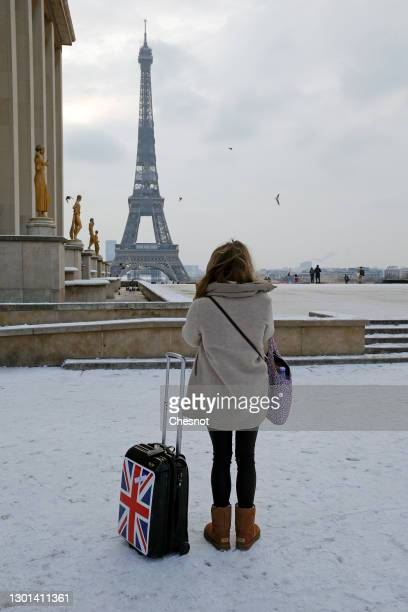 Woman looks at the Eiffel Tower on the square of the Trocadero covered in snow following a light overnight snowfall on February 10, 2021 in Paris,...