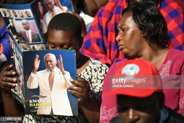 A woman looks at the funeral programme booklet of late former Kenya President Daniel Arap Moi during the state funeral service in Nairobi on February...