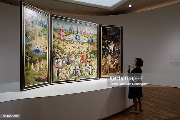 A woman looks at 'The garden of earthly delights triptych' by Dutch painter Hieronymus Bosch during a press preview of the 'El Bosco' 5th Centenary...