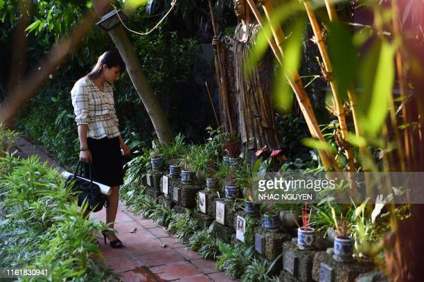 A woman looks at the grave of dogs and cats at Te Dong Vat Nga pagoda which means all lives are equal a cemetary for pets in Hanoi on August 15 2019...