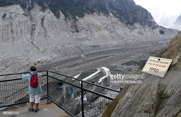 A woman looks at the 'La Grotte de glace' of the 'Mer de Glace' glacier next to a sign showing the glacier's ice level in 1990 on June 8 in...