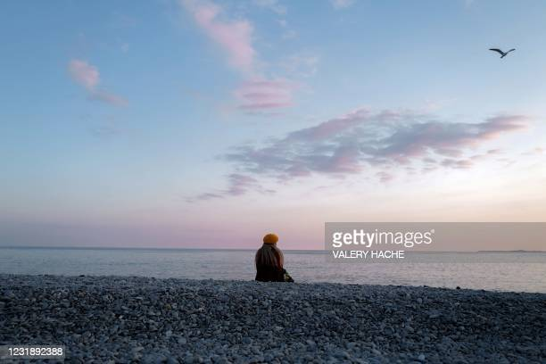 Woman looks at the Mediterranean sea from the beach on the French riviera city of Nice, on March 23, 2021.