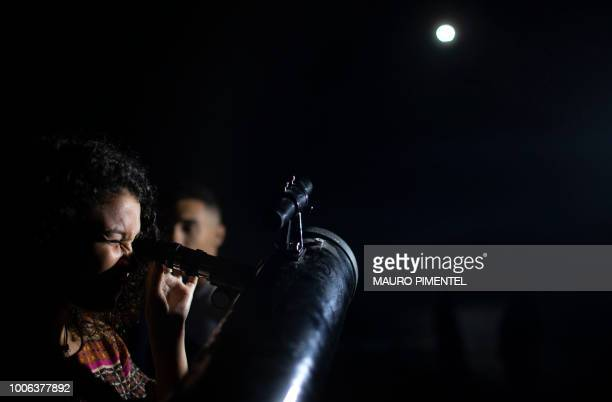 A woman looks at the moon eclipse through a telescope at Copacabana Fortress in Rio de Janeiro Brazil on July 27 2018 The longest 'blood moon'...