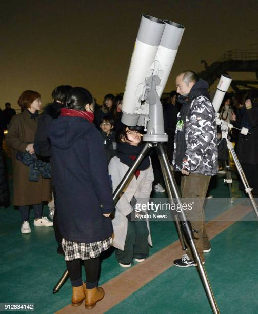 A woman looks at the moon through a telescope during an event to observe a total lunar eclipse in Tokyo on Jan 31 2018 ==Kyodo