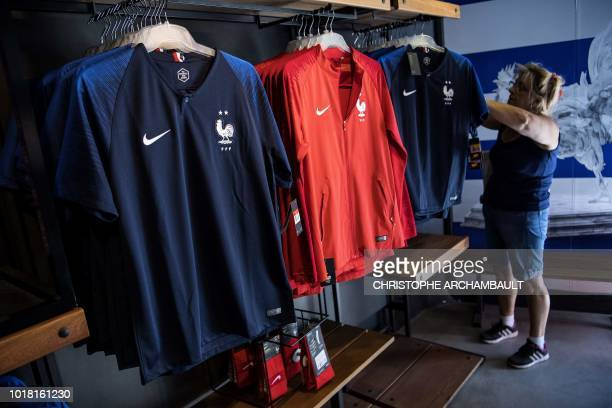 A woman looks at the new jersey of the French national football team bearing the two stars of world champion displayed for sale at the French...