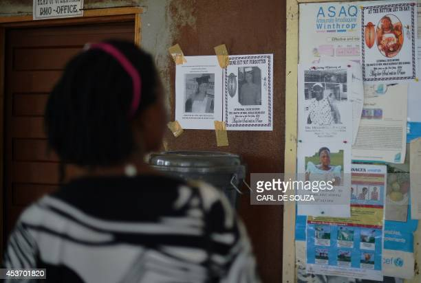 A woman looks at the obituary notices for medical staff who have died from the Ebola virus at the Kenema government hospital in Sierra Leone on...
