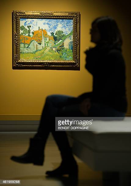 A woman looks at the painting called Street in AuverssurOise Rue a AuverssurOise Straat in AuverssurOise in the exhibition Van Gogh in de Borinage in...