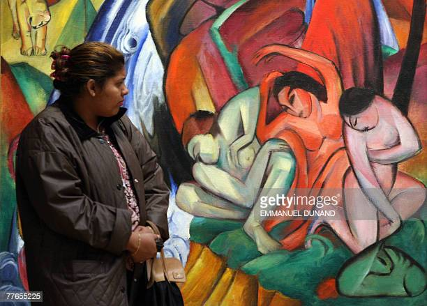 A woman looks at the painting Der Wasserfall by German artist Franz Marc during a preview of Sotheby's fall sales of impressionist and modern art in...
