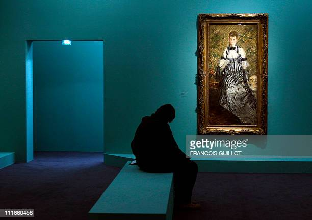 A woman looks at the painting Femme en robe de soiree made between 1877 and 1880 by French impressionist artist Edouard Manet during the press visit...