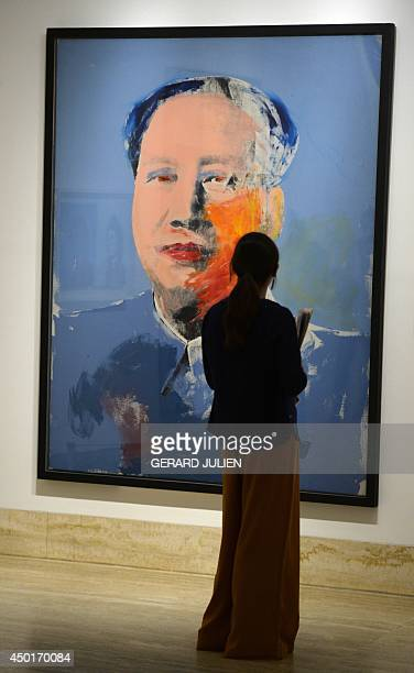 A woman looks at the painting 'Mao' by US artist Andy Warhol during an exhibition titled 'Pop Art Myths' at the ThyssenBornemisza museum in Madrid on...