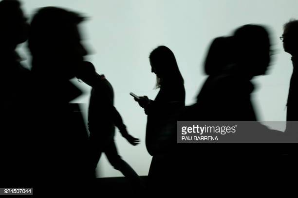 A woman looks at the phone at the Mobile World Congress the world's biggest mobile fair on February 26 2018 in Barcelona the Mobile World Congress is...