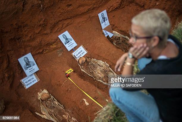 A woman looks at the remains of the 14 political prisoners bodies hanged under the apartheid in 1964 on December 14 at the Rebecca cemetery in...