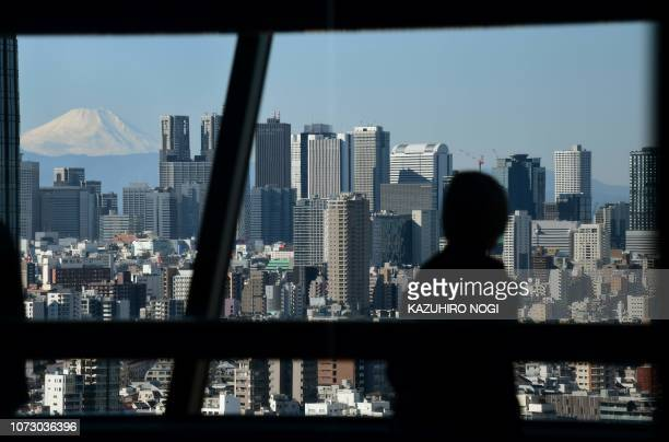 A woman looks at the scenery of the city and a snowcapped Mount Fuji in the distance from the observation deck of a skyscraper in Tokyo on December...