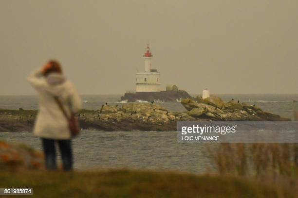A woman looks at the Teignouse lighthouse on October 16 in Quiberon western France as the sky turned a yellowochre colour due to sand from the Sahara...