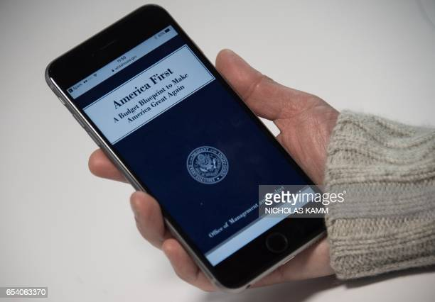A woman looks at the title page of US President Donald Trump's proposed budget on the White House website on a smartphone in Washington DC on March...