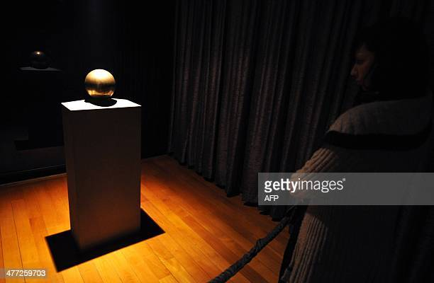 A woman looks at the urn containing the ashes of Serbian inventor Nikola Tesla at the museum bearing his name in Belgrade on March 8 2014 Several...