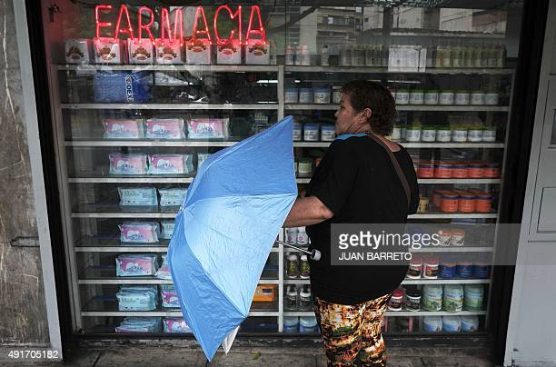 A woman looks at the window of a pharmacy in one of the main streets of Caracas on October 7 2015 Venezuelan President Nicolas Maduro said Tuesday...