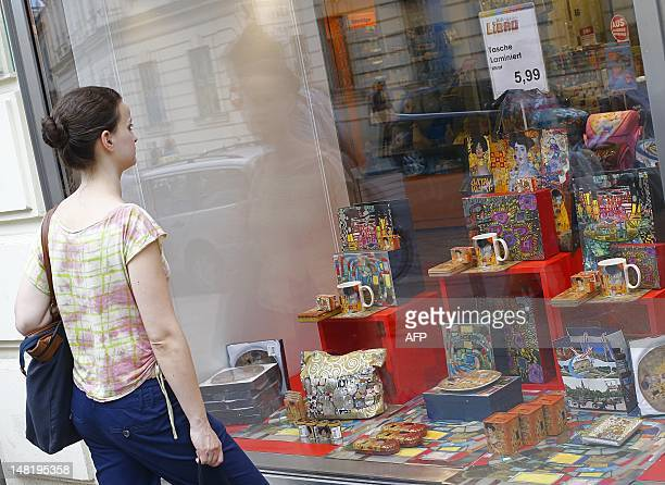 A woman looks at the window of a shop with various souvenirs of Austrian artist Gustav Klimt in Vienna on July 11 2012 On his 150th birthday Vienna's...