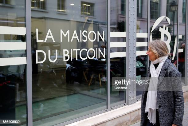 A woman looks at the window of the offices of the bank 'La Maison du Bitcoin' on December 05 2017 in Paris France The value of the digital...