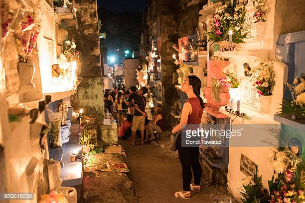A woman looks at tombstones at a public cemetery on November 1 2016 in Manila Philippines Filipinos flock to cemeteries around the country to visit...