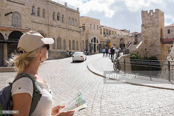 Woman looks at tourist map on city street