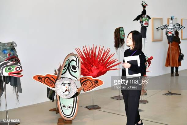A woman looks at twenty masks from the series 'Undersea Kingdomâ' by artist Beau Dick on June 7 2017 in Kassel Germany The documenta 14 is the...