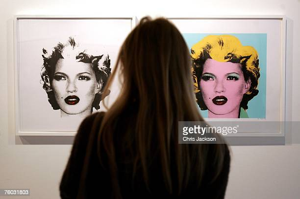 A woman looks at two screen prints of Kate Moss done in the style of Warhol's iconic Marilyn Monroe portraits by Banksy at the Warhol vs Banksy...