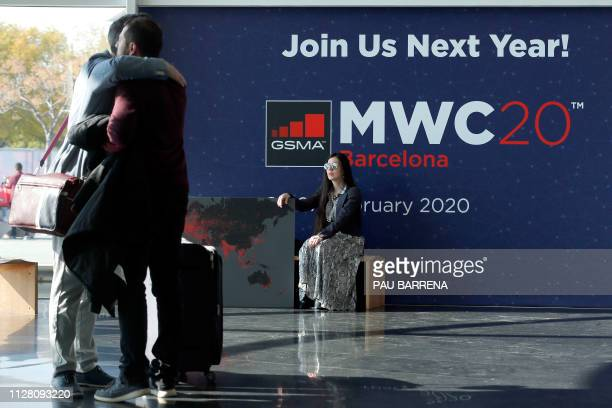A woman looks at two visitors hugging each other on the last day of the Mobile World Congress in Barcelona on February 28 2019 Phone makers focused...