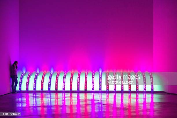 A woman looks at US artist Jenny Holzer's 'Purple' during a presentation of the 'Jenny Holzer Thing Indescribable' exhibition at the Guggenheim...