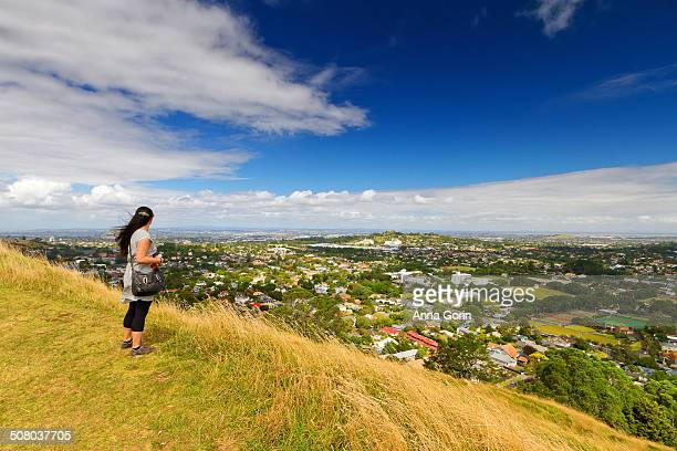 Woman looks at view of Auckland from Mount Eden