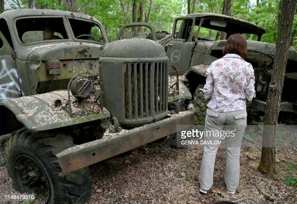 A woman looks at wreckage of trucks in the ghost city of Pripyat during a tour in the Chernobyl exclusion zone on June 7 2019 HBOs hugely popular...